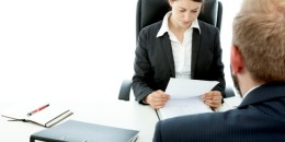 beard business man brunette woman at desk read contract
